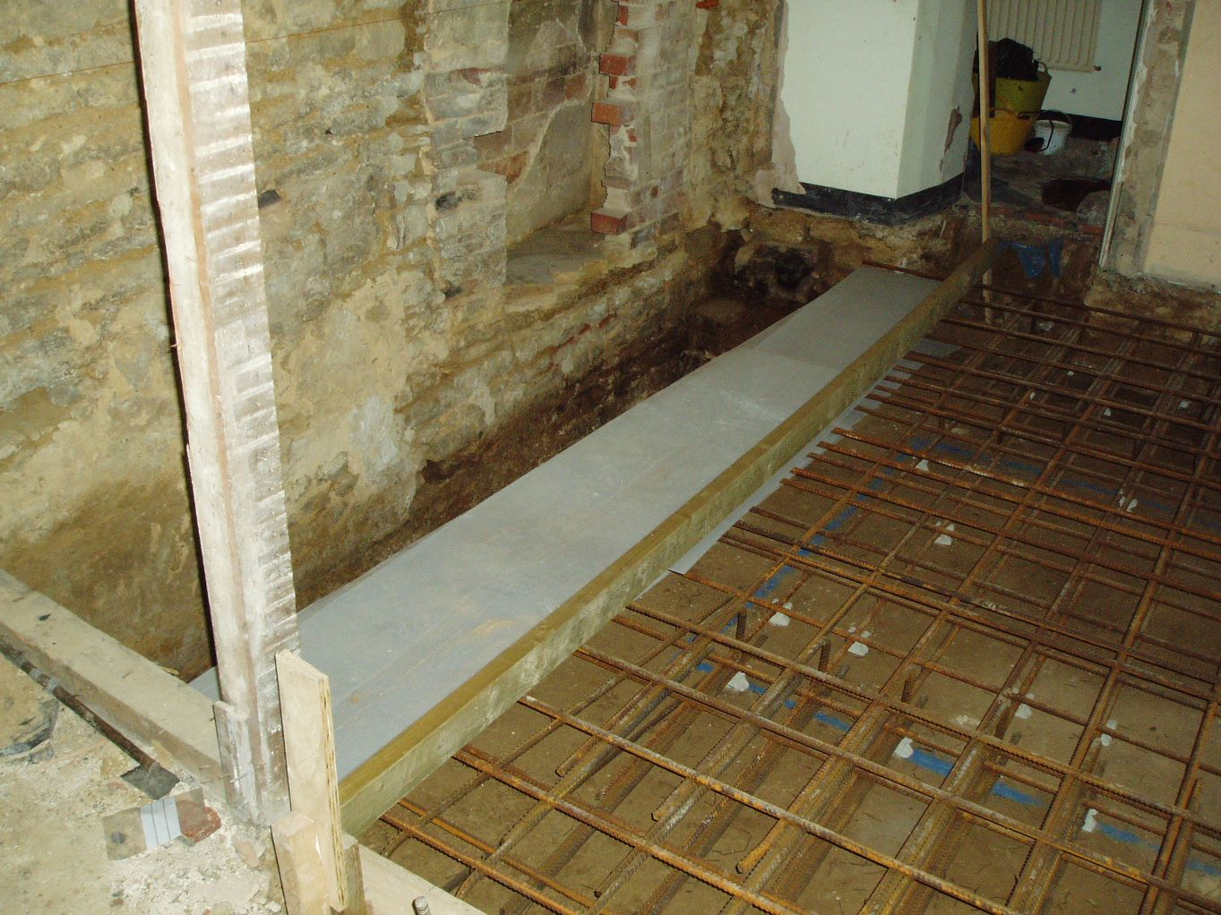 The medieval wall and floor revealed to the left of the lift base