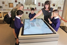 Schoolchildren doing the quiz on the digital touch table