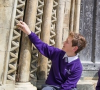 A student examining the carved stonework outside the Cathedral
